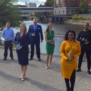 group of the regions top young professionals honored at 10 over the next ten awards holding their trophies in front of the river