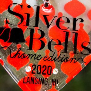 "a heart ornament hanging from a christmas tree that says ""Silver Bells Home Edition 2020 Lansing, MI"""